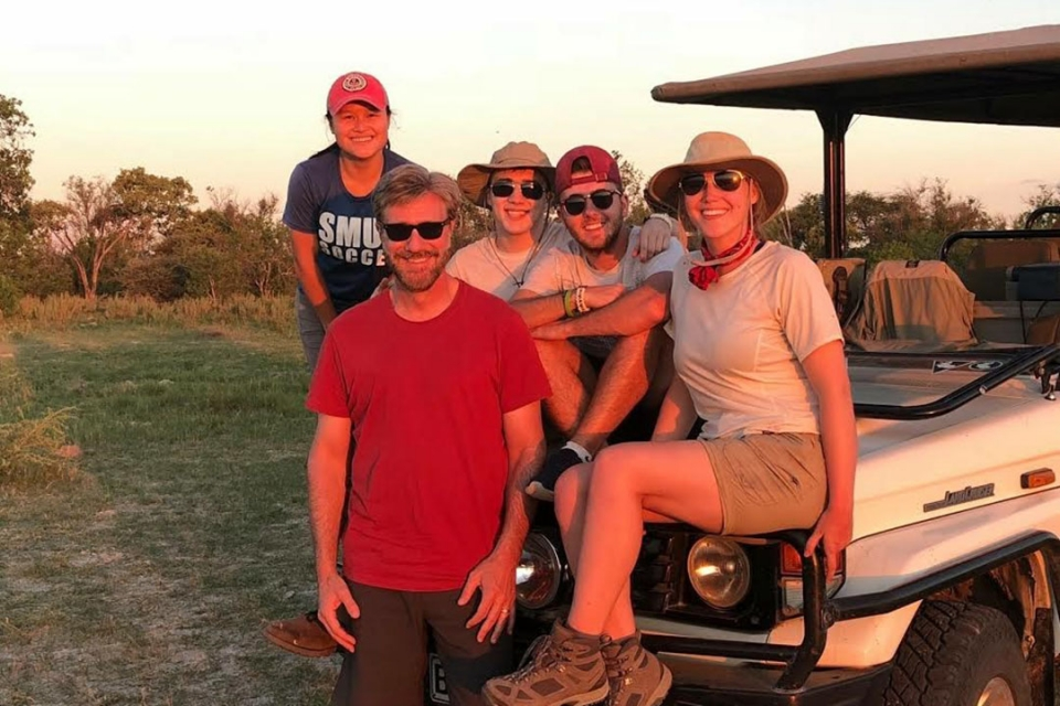 Joseph Dymond and four students sitting outside in the Botswana plains around a jeep